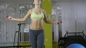 Retrato completo do comprimento de uma mulher alegre que faz exercícios com a corda de salto isolada em um fundo branco vista video estoque