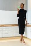 Retrato completo do comprimento de uma mulher de negócios que veste o vestido preto e as sapatas bege que guardam o copo descartá fotos de stock royalty free