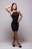 Retrato completo do comprimento de uma mulher 'sexy' em pouco vestido preto da forma no cinza Imagens de Stock
