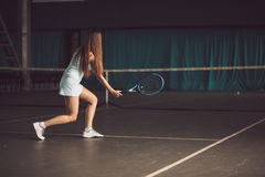 Retrato completo do corpo do jogador de tênis da moça na ação em um campo de tênis interno Foto de Stock Royalty Free