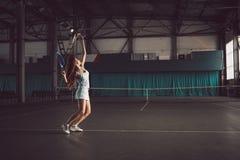 Retrato completo do corpo do jogador de tênis da moça na ação em um campo de tênis interno Imagem de Stock