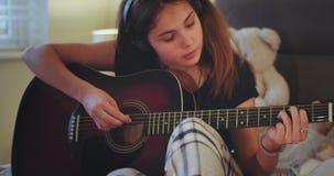 Retrato con una señora joven que juega en una guitarra en su sitio muy concentrado y la sonrisa linda delante de la cámara almacen de metraje de vídeo