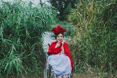Retrato conceptual da jovem mulher bonita com bordos vermelhos, flores vermelhas no cabelo, sentando-se na cadeira de roda fotos de stock royalty free