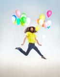 Retrato conceptual de un hombre infantil que salta con los globos imagen de archivo
