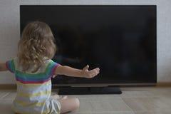 Retrato conceptual A menina que a menina espalhou seus braços para fora aos lados senta-se no fundo de uma tela preta da tevê Fotos de Stock