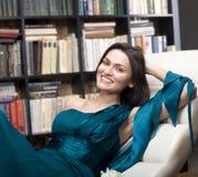 Retrato conservado em estoque da foto do livro de leitura da jovem mulher da beleza na biblioteca Fotos de Stock