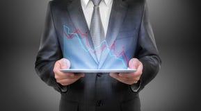 Retrato cosechado de una tableta de la tenencia del hombre de negocios con el diagrama que cae sobre él Imagenes de archivo