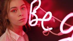 Retrato creativo de la muchacha hermosa cerca de la pared ligera de neón roja metrajes