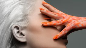 Retrato criativo de uma menina bonita com mão na cara, cabelo branco A mão é pintada com pintura alaranjada foto de stock