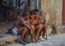 Retrato cubano pobre de la captura del muchacho en callejón colonial tradicional con viejo estilo de vida, en La Habana vieja, Cu imagen de archivo libre de regalías