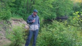 Retrato da água potável nova do homem do turista na floresta perto do rio, exterior filme