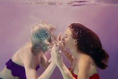 Retrato da arte de duas meninas bonitas bonitas que mantêm-se mãos subaquático Fotos de Stock