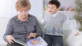 Retrato da avó e do neto que leem um livro no berçário fotos de stock