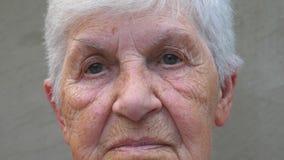 Retrato da avó idosa com uma vista triste Cara enrugada da senhora idosa que olha na câmera Amargura facial filme