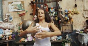 Retrato da bailarina consideravelmente pequena que executa truques com uma bola de prata no fundo dos brinquedos velhos que decor video estoque