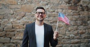 Retrato da bandeira de ondulação dos E.U. do oficial do homem americano feliz que sorri fora filme