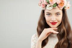 Retrato da beleza de mola da mulher modelo nova perfeita A menina bonita com composição vermelha dos bordos e as flores envolvem  imagem de stock royalty free
