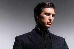 Retrato da beleza de um modelo masculino no terno preto, penteado, olhando olhando de sobrancelhas franzidas, em um fundo branco imagens de stock royalty free