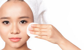 Retrato da beleza de uma jovem mulher asiática que limpa a cara com o algodão Fotos de Stock