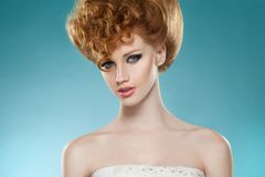 Retrato da beleza de uma menina hairred vermelha com hairdressed e salpico, com os ombros despidos, isolados em um fundo azul imagem de stock