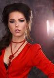 Retrato da beleza de uma morena 'sexy' bonita em um vestido vermelho em um fundo cinzento Fotografia de Stock Royalty Free