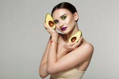 Retrato da beleza de uma mulher saudável atrativa com o abacate fresco cortado nas mãos cruzadas perto da cara fotos de stock