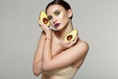 Retrato da beleza de uma mulher saudável atrativa com o abacate fresco cortado nas mãos cruzadas perto da cara imagens de stock