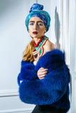 Retrato da beleza do modelo de forma com headwear colorido, sobrancelha vermelha do casaco de pele azul e composição e colar dos  Foto de Stock Royalty Free