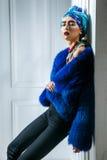 Retrato da beleza do modelo de forma com headwear colorido, sobrancelha vermelha do casaco de pele azul e composição e colar dos  imagens de stock royalty free