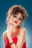 Retrato da beleza. Mulher bonita no vestido vermelho que toca em sua cara. foto de stock