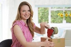 Retrato da caixa de selagem da mulher em casa para a expedição Imagens de Stock Royalty Free