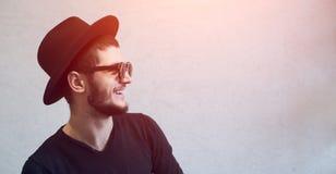 Retrato da cara do perfil de rir o indivíduo novo do moderno sobre o fundo branco do estúdio Óculos de sol e chapéu negro vestind imagem de stock