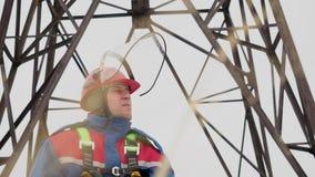 Retrato da cara da posição do eletricista no fundo elétrico da torre video estoque