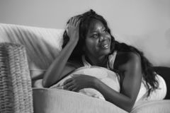 Retrato da casa do estilo de vida da mulher afro-americana preta bonita e feliz nova que encontra-se no sorriso do sofá da sala d foto de stock royalty free