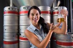 Retrato da cerveja de exame de sorriso do trabalhador na taça na fábrica imagem de stock royalty free
