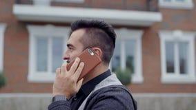 Retrato da cidade de um homem com um telefone Um homem com uma barba que fala no telefone vídeos de arquivo