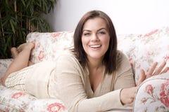 Retrato da colocação de sorriso da jovem mulher bonita no sofá Fotografia de Stock