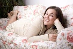 Retrato da colocação de sorriso da jovem mulher bonita no sofá Foto de Stock Royalty Free