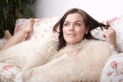 Retrato da colocação de sorriso da jovem mulher bonita no sofá Imagem de Stock Royalty Free
