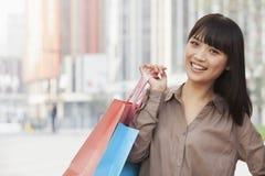Retrato da compra indo feliz, das jovens mulheres e de guardarar sacos de compras coloridos na rua no Pequim, China Imagens de Stock