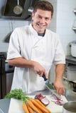 Retrato da cozinha do restaurante de Preparing Vegetables In do cozinheiro chefe fotos de stock
