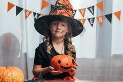 retrato da criança adorável na abóbora da terra arrendada do traje do Dia das Bruxas da bruxa imagem de stock