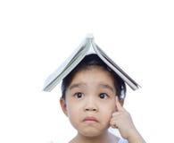 Retrato da criança asiática pequena que pensa e posta um livro sobre a parte superior foto de stock