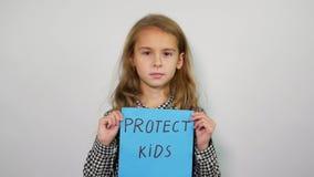 Retrato da criança bonita com slogan para proteger crianças vídeos de arquivo