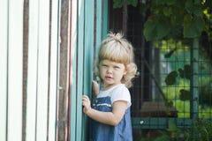 Retrato da criança bonita com um cabelo encaracolado sobre uma cerca fotografia de stock royalty free
