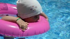 Retrato da criança caucasiano branca feliz do bebê da criança na piscina exterior Treinamento pré-escolar do menino a flutuar com filme