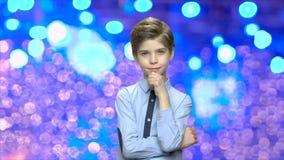 Retrato da criança considerável no fundo azul do bokeh filme