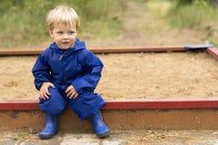 Retrato da criança da criança fora Bebê da criança de dois anos que senta-se no campo de jogos na caixa de areia Copie o espaço Fotos de Stock Royalty Free