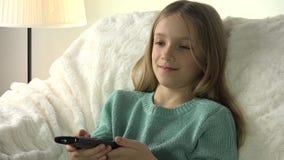 Retrato da criança que olha a tevê, menina com relaxamento de controle remoto no sofá, treinador 4K vídeos de arquivo
