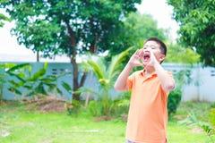 Retrato da criança asiática que grita, gritando, gritaria, mão em olá! Fotos de Stock